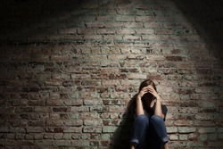 Sad woman sitting alone against brick wall.