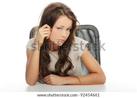 Sad woman sitting behind the desk, isolated on white
