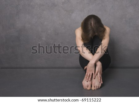 Sad woman sitting on a floor near concrete wall, studio shot