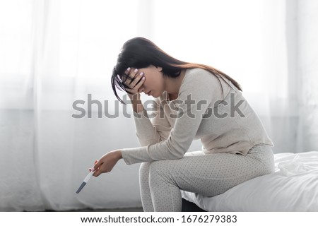 sad woman sitting on bed and holding pregnancy test with negative result
