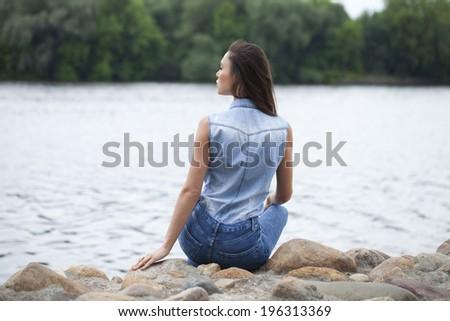 Sad woman sitting on rocks on the river