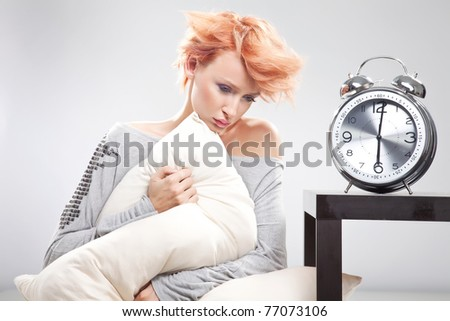 Sad woman sitting on the bed - stock photo
