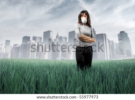 Sad woman wearing a surgical mask with polluted green meadow and city on the background