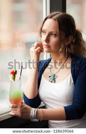 Sad woman with cocktail looking out the window