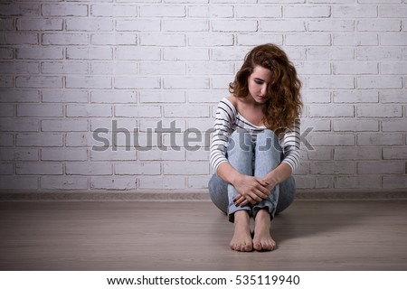 sad woman with depression or headache sitting on the floor over white brick wall