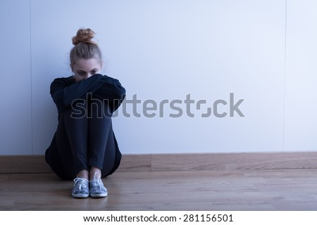 Sad woman with depression sitting on the floor