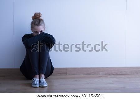 Sad woman with depression sitting on the floor