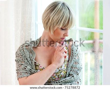 sad woman with mobile phone next to window - stock photo