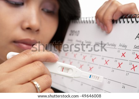 stock photo : Sad woman with negative pregnancy test and calendar.