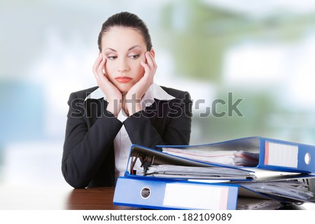 Sad woman with ring binders sitting at the desk. Tired and exhousted business woman.