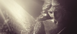 Sad wonderful angel in the rays of the sun. Antique statue.Horizontal image.
