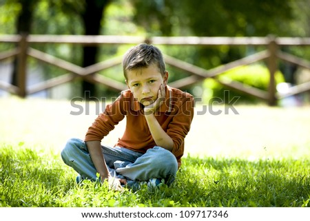 Sad/worried little boy sitting outdoors
