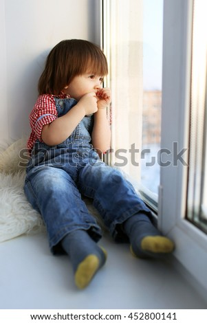 Sad 2 years boy sits on sill and looks out of window in wintertime #452800141