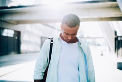 Sad young African American male in white t shirt and shirt with backpack walking on city street near bridge and building in sunny summer day