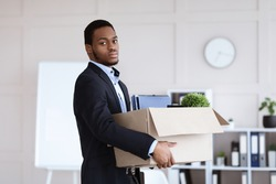 Sad young black man got fired, standing in office and holding box with his belongings, copy space. Terminated african american guy in suit lost his job, packing working stuff before leaving workplace
