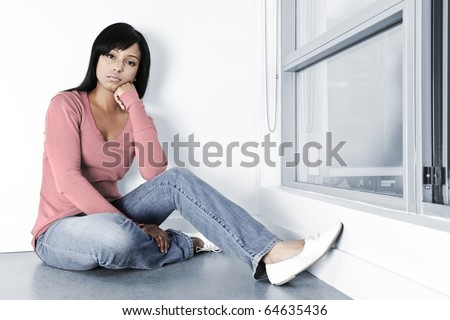 Sad young black woman sitting against wall on floor