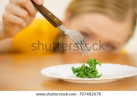Sad young blonde woman dealing with anorexia nervosa or builimia having small green vegetable on plate. Dieting problems, eating disorder. #707482678