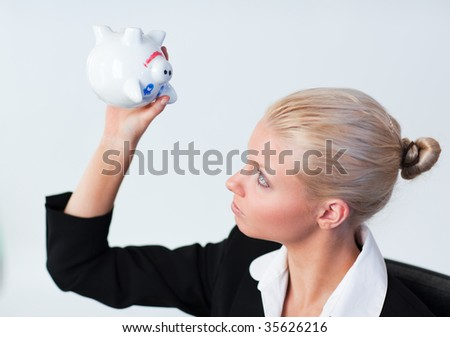 Sad young Business woman looking into Piggy Bank