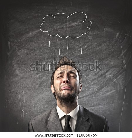Sad young businessman with raincloud over his head - stock photo