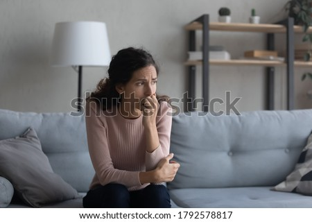 Sad young Caucasian woman sit on couch at home look in distance mourning yearning, unhappy upset female thinking suffering from relationships problems, struggle with miscarriage or abortion trouble
