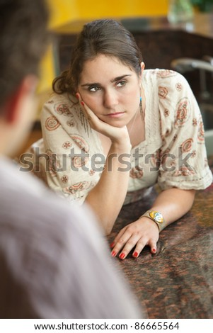 Sad young Caucasian woman with hand on chin in kitchen with friend