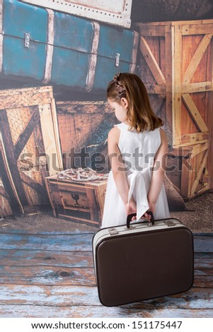 Sad young child holding a suitcase