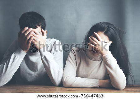 sad young couple sitting in table on dark background