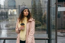 Sad young curly  woman with cup of coffee stay at the bus stop in rainy day