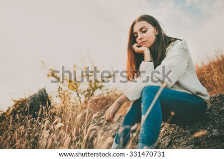 Sad young girl sitting alone on a stone outdoors. Teenage girl thinking thoughtfully. Hope. Sadness. Loneliness