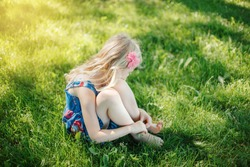 Sad young girl sitting on ground outdoor on summer sunny day. Pensive little child dreaming thinking. Insecure lonely kid trying to cope with stress problems. Authentic childhood lifestyle.