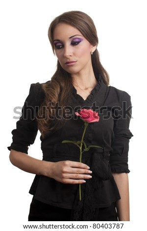 Sad young girl with a red rose in hand