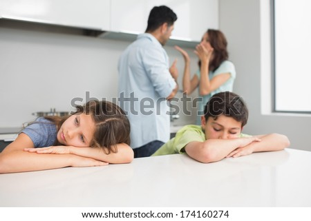 Sad young kids while parents quarreling in the kitchen at home