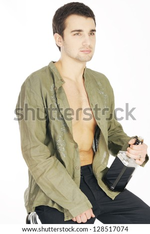 Sad young man holding a bottle of whiskey on a white background