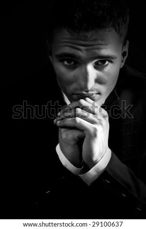Sad young man in the dark praying to God