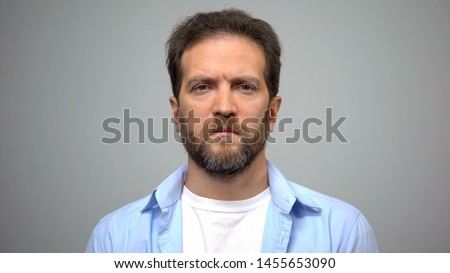 Sad young man on grey background, male loneliness, suffering breakup depression #1455653090