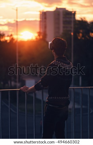 sad young man trying a pair of VR glasses raising one hand dressed in a cool sweater and trendy outfit excited by augmented reality sunlit by an amazing sunset from background low light soft focus