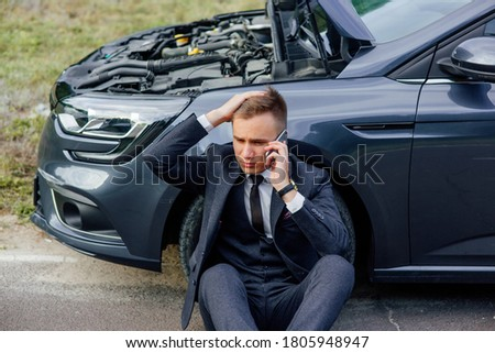 sad young man use smartphone sitting on road near the broken car opened the hood, calling car assistance services, help repair stress problem emergency insurance aut. Stock fotó ©