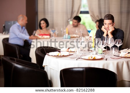 sad young man waiting date restaurant table
