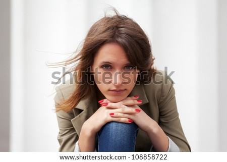 Sad young woman against a white wall