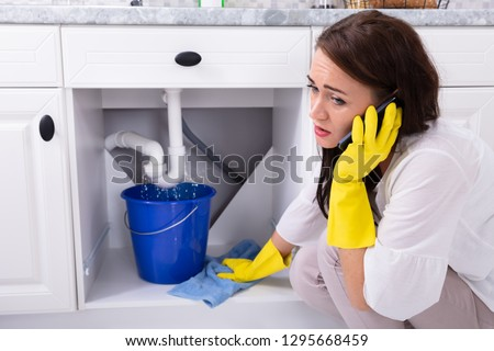 Sad Young Woman Calling Plumber In Front Of Water Leaking From Sink Pipe #1295668459