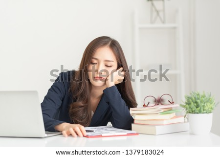 Sad Young woman employee having problems about her debts and financials. Frustrated Asian Beautiful businesswoman feeling depression, exhausted, tired, lazy during working at the office.