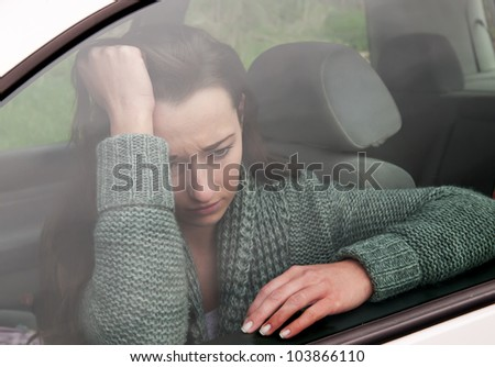 sad young woman in the car