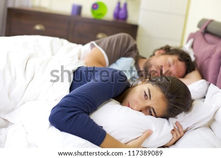 sad young woman laying in bed crying after fight with husband