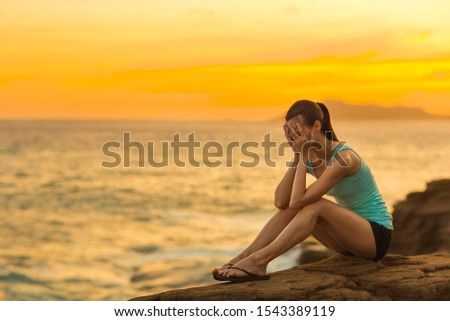 Sad young woman sitting alone on the ocean coast rocks during sunset.