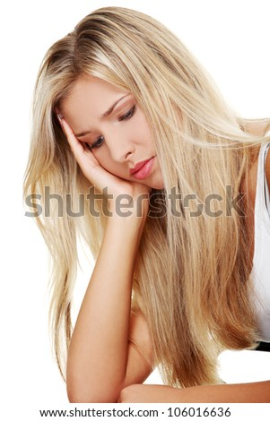 Sad, young woman with blond long hair is sitting and thinking looking down.