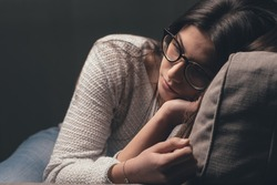 Sad young woman with glasses sitting on the couch at home, she is depressed and lonely