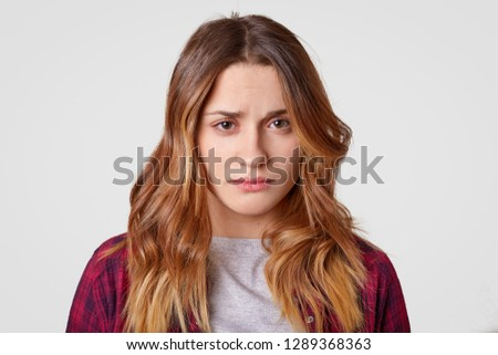Sad young woman with sorrowful expression feels frustrated, has long hair, has healthy skin, expresses sadness and sorrow, isolated over white background. People and negative emotions concept.