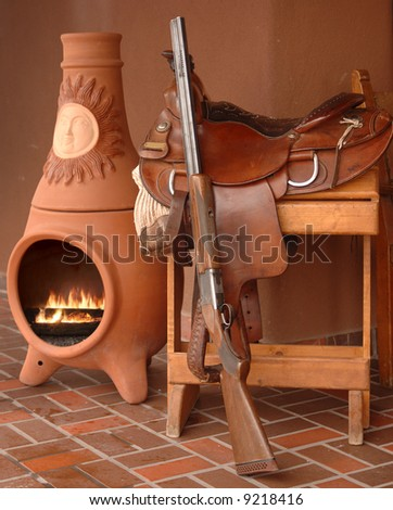 Saddle, rifle and kiva fireplace still life depicting New Mexico