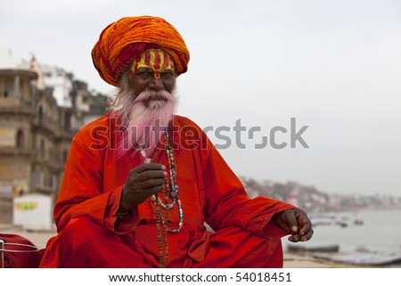 Sadhu at the ghats in Varanasi India With a pink beard from the traditional holi festival.