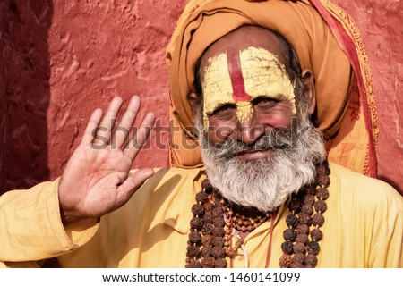 Sadhu man with traditional painted face in Pashupatinath Temple of Kathmandu, Nepal.Sadhu man refer to holy person.Nepal text in photo refer to prayer word om mani padme hum - Film grain effect #1460141099